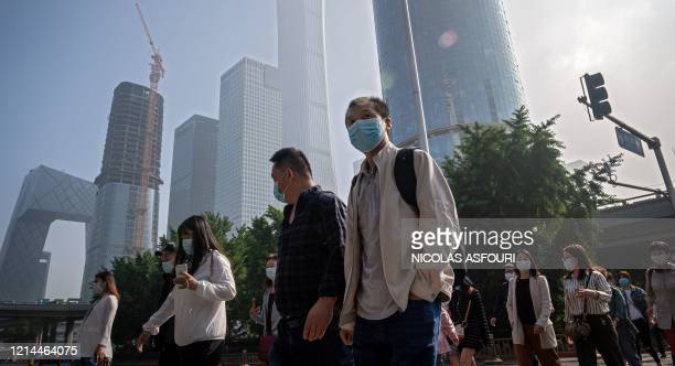 People commute during the morning rush hour before the opening session of the National People's Congress in Beijing on May 22, 2020. - China took the...