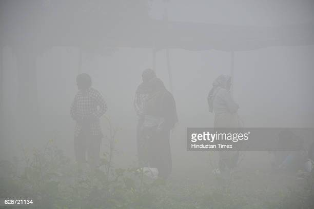 People commute in heavy fog at Dasna village near NH 24 on December 9 2016 in Ghaziabad India Fog continued to engulf Delhi on Friday morning...