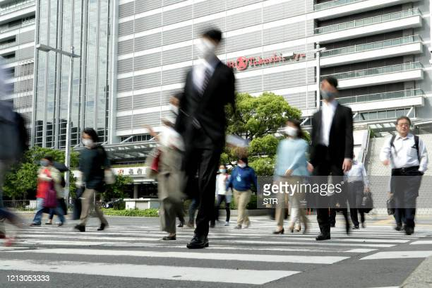 People commute to work as they cross a street connecting from Nagoya train station in Nagoya, Aichi prefecture on May 15 a day after a state of...