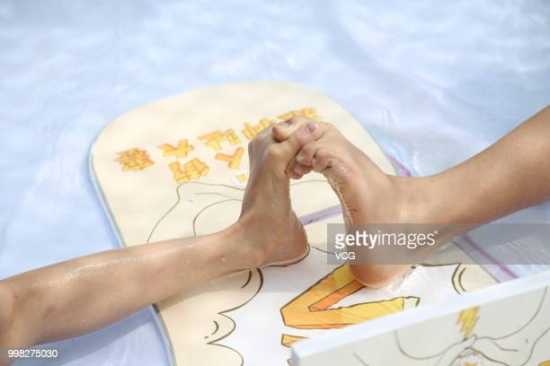 People compete in a toe wrestling competition at a water park on July 11, 2018 in Chongqing, China.