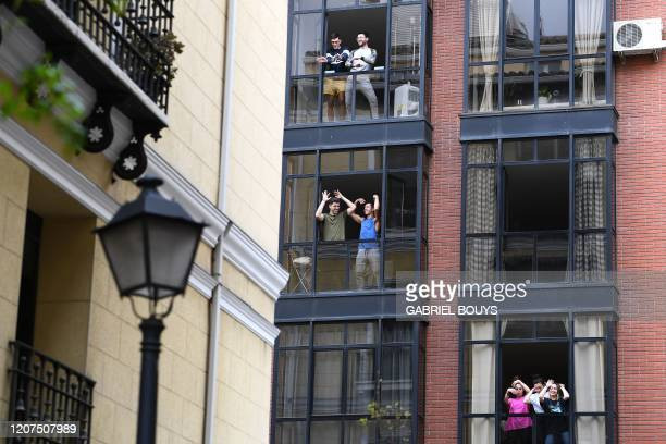 TOPSHOT People confined at their homes sing and dance from their windows to bolster themselves up on March 17 2020 during a lockdown in Madrid as...