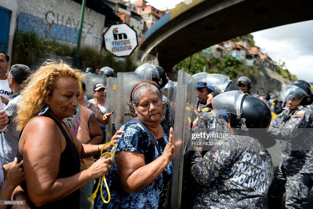People confront riot police during a protest against the shortage of food, amid Fuerzas Armadas avenue in Caracas on December 28, 2017. As Venezuelans protest in Caracas demanding the government's prommised pork -the main dish of the Christmas and New Year's dinner-, President Nicolas Maduro attributes the shortage to international sabotage. /