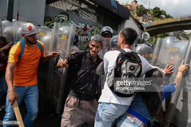 TOPSHOT People confront riot police during a protest against the shortage of food amid Fuerzas Armadas avenue in Caracas on December 28 2017 As...