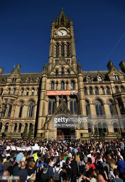 People congregate outs ie the Town Hall for a vigil in Albert Square in Manchester northwest England on May 23 in solidarity with those killed an...
