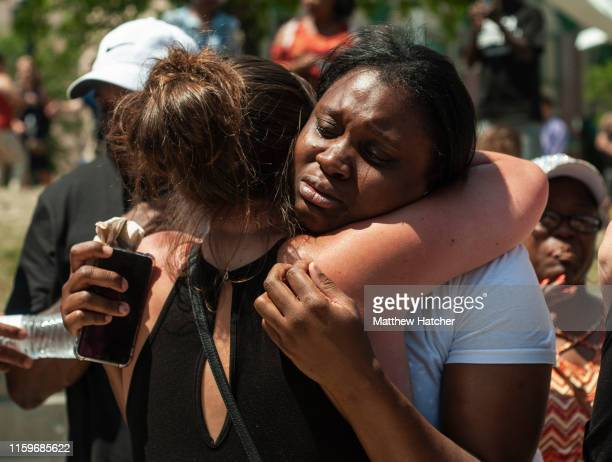 People console each other as they gather for a vigil for the victims of the mass shooting that occurred over night, at the Levitt Pavilion on August...