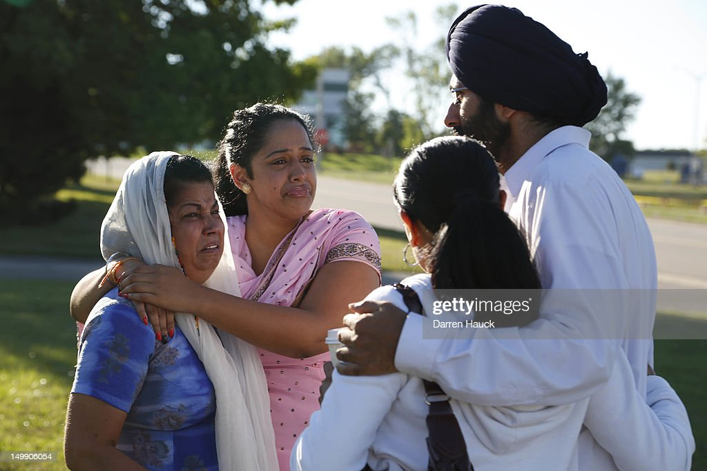 People console each other at the command center near the Sikh Temple of Wisconsin where yesterday a gunman fired upon people at service August, 6, 2012 Oak Creek, Wisconsin. At least six people were killed when a shooter opened fire on congregants in the Milwaukee suburb. The shooter who was later shot dead by a police officer.