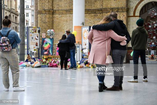 People console each other in front of the floral memorial at Victoria station during the commemoration People gather at Victoria station to mark the...