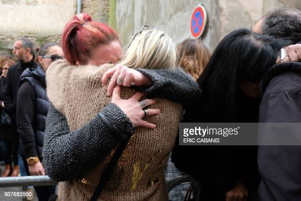 People console each other outside the Saint Etienne Church in Trebes in southwest France after a service of remembrance to victims on March 25 two...
