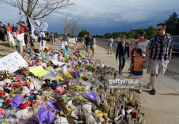 People continue to visit the roadside memorial set up for victims of the Colorado theater shooting massacre across the street from Century 16 movie...