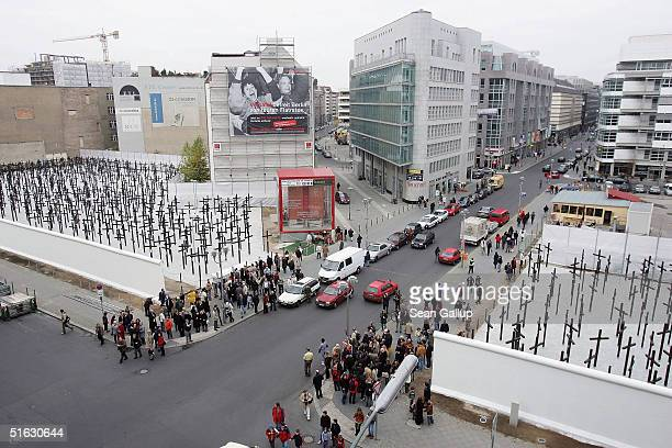 People converge at a rebuilt section of the Berlin Wall and crosses that commemorate its victims on the day of the memorial's unveiling on October 31...