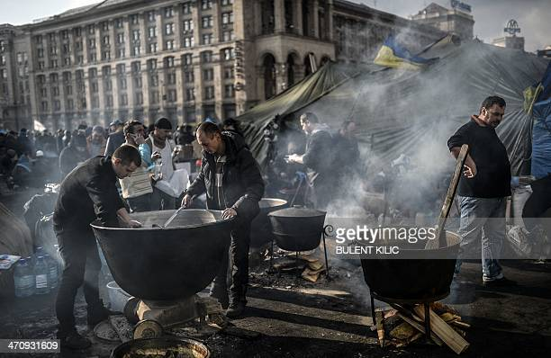 People cook for protesters on Independence square on February 21 2014 in Kiev Ukrainian President Viktor Yanukovych and three main opposition leaders...