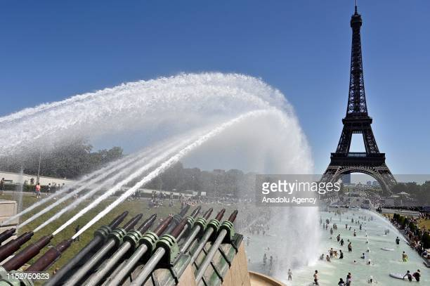 People cool down in the fountains of Trocadero near the Eiffel Tower during a heatwave in Paris, France on June 29, 2019.