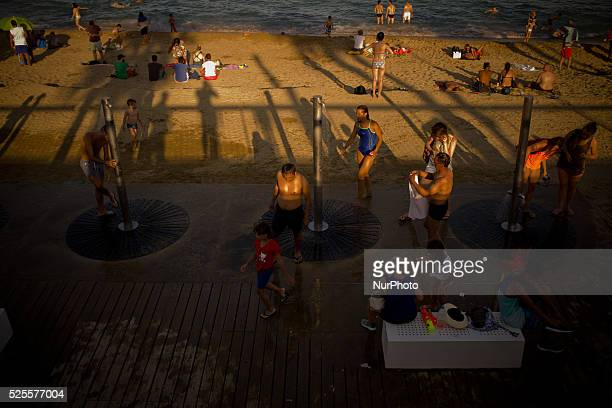 People cool in showers and sea at Barcelona beach as the sun sets on 10 July 2015