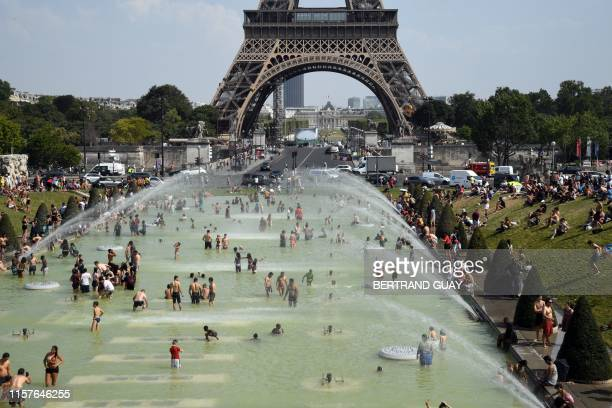 People cool off and sunbathe at the Trocadero Fountains in Paris on July 25 2019 as a new heatwave hits the French capital After alltime temperature...