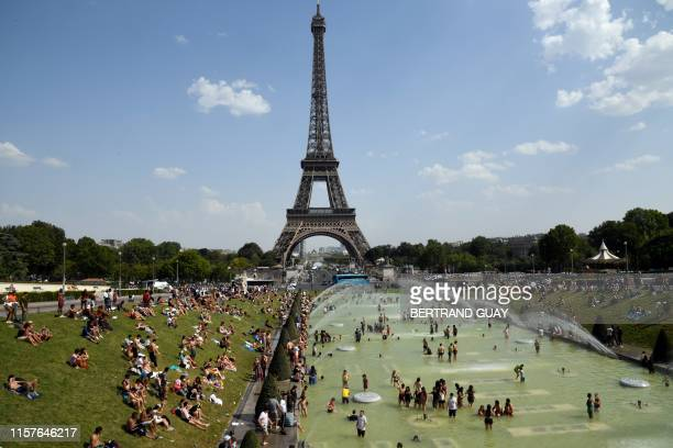 TOPSHOT People cool off and sunbathe by the Trocadero Fountains next to the Eiffel Tower in Paris on July 25 2019 as a new heatwave hits the French...