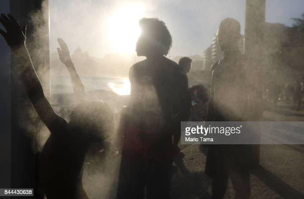 People cool off at a cooling station on a hot winter day on Ipanema beach on the Atlantic Ocean on September 8 2017 in Rio de Janeiro Brazil...
