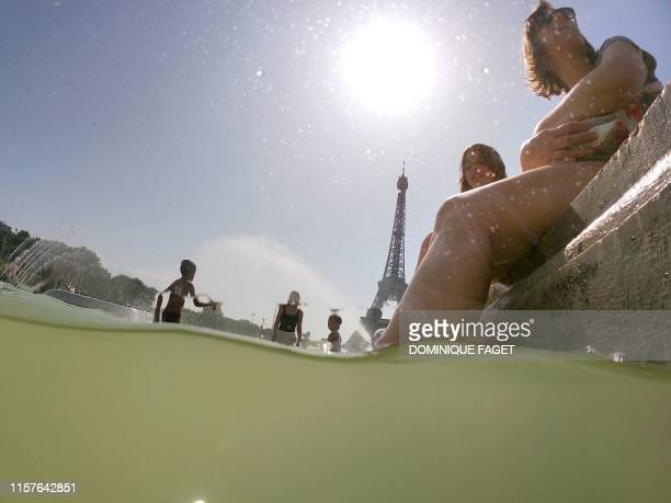 People cool off at the Trocadero Fountains next to the Eiffel Tower in Paris on July 25 2019 as a new heatwave hits Europe After alltime temperature...
