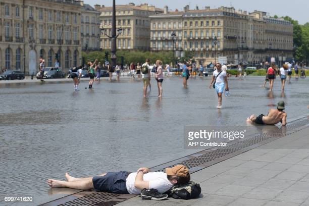 People cool off at the water mirror fountain whose system alternates a mirror effect with a mist effect on June 22 2017 in Bordeaux's city center...