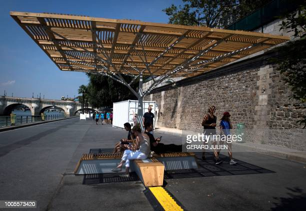People cool off below a Cooling Island designed by Climespace and installed in partnership with the Eau de Paris on the River Seine on July 26 during...