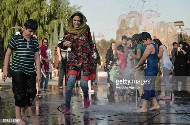 People cool off in a fountain at a park in Tehran Iran on July 15 2016