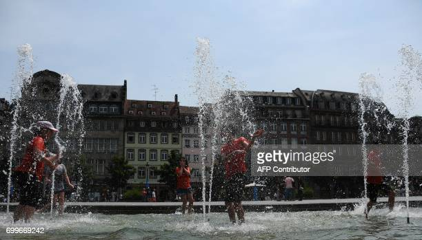 People cool off in a fountain in Strasbourg northeastern France on June 22 as temperatures climb across Europe Europe continued to sizzle in a...