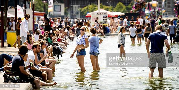 People cool off in a fountain on Museum square in Amsterdam the Netherlands on July 1 on a hot summer day A blistering heatwave sweeping through...