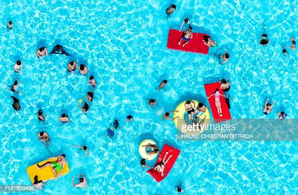 TOPSHOT People cool off in a swimming pool in Hannover western Germany on June 25 2019 as temperatures topped 33 degrees Celsius Europeans are set to...