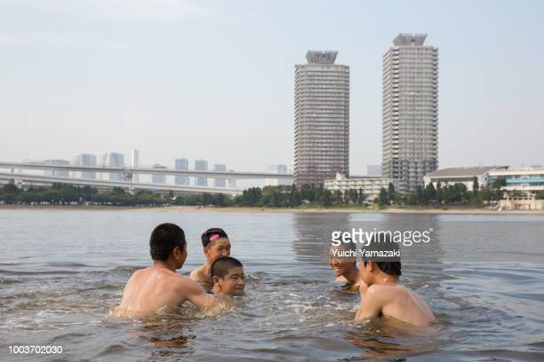 People cool off in Odaiba kaihin park on July 22 2018 in Odaiba Tokyo Japan A deadly heatwave which has killed at least 30 people continues to grip...