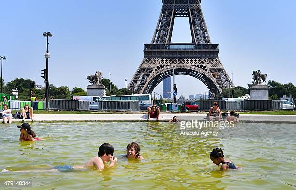 People cool off in ponds around Eiffel Tower in Paris where temperatures hit somewhere mid40deg C on July 1 2015