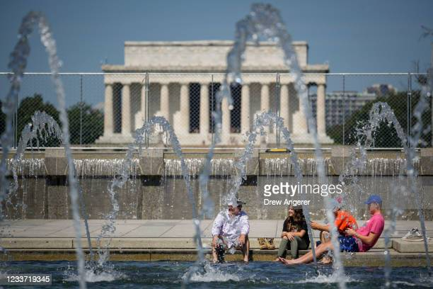 People cool off in the fountains at the World War II Memorial on the National Mall June 29, 2021 in Washington, DC. Temperatures will climb into the...
