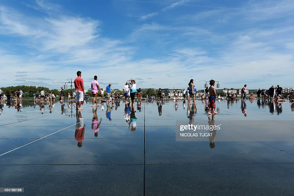 People cool off in the Water Mirror on August 25, 2014 in the southwestern French city of Bordeaux. Hardly eight years after its creation, the Water Mirror is taking an amazing place in the daily lives of Bordeaux residents.