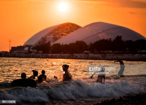 People cool off in the waves from the Black sea as the sun sets behind Fisht Olympic stadium in Sochi on June 25 2018 The stadium is host to some of...