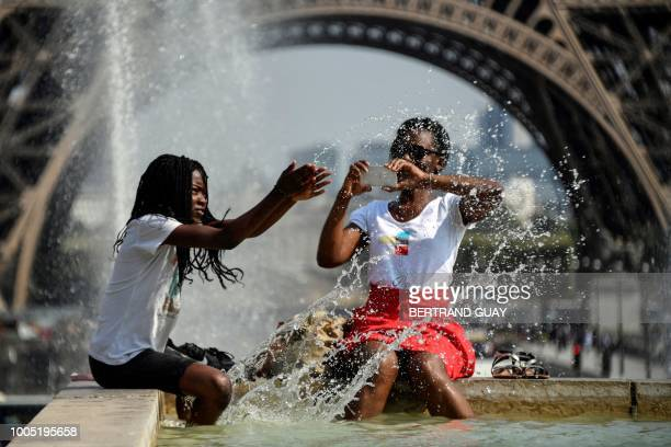 People cool themselves at the Fontaine du Trocadero in front of The Eiffel Tower in Paris on July 25 as a heatwave continues across northern Europe...