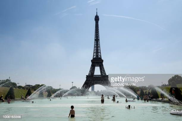 People cool themselves at the Trocadero Fountain in front of The Eiffel Tower in Paris on July 27 as a heatwave continues across northern Europe