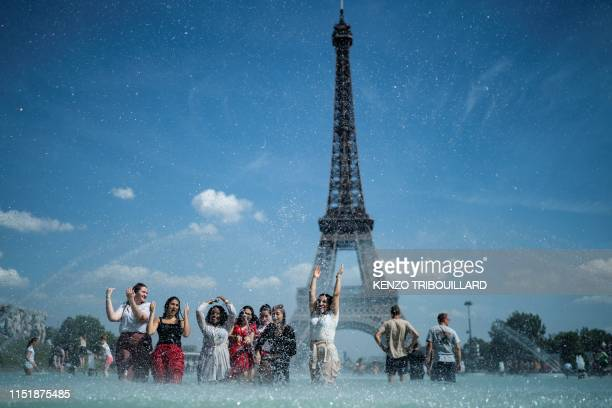People cool themselves down in the fountain of the Trocadero esplanade in Paris on June 25, 2019 with the Eiffel Tower on the background. -...