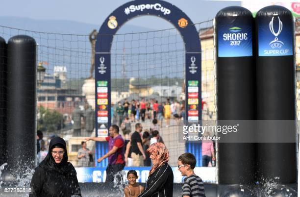 People cool themselves next to a fountain in the UEFA Super Cup fan zone in Skopje on August 7 on the eve of the UEFA Super Cup match between Real...