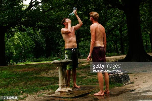 People cool theyself after playing beach volleyball at Central Park on August 17 2018 in New York City Severe thunderstorms and even an isolated...