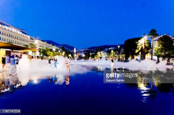 people cooling off from the summer heat at promenade du paillon reflecting pool at dusk - nice, france - mirror steam stock photos and pictures