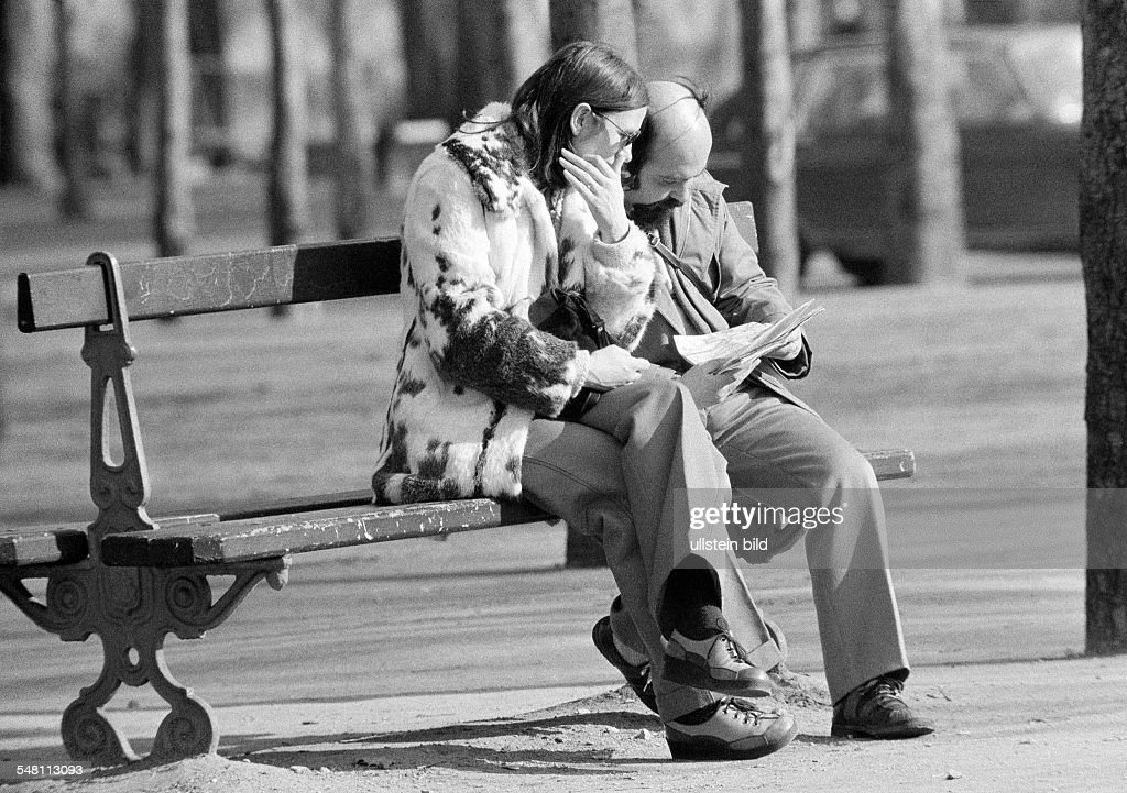 people, couple sits on a bench viewing a road map, aged 30 to 40 years, France, Paris - 09.02.1975 : News Photo