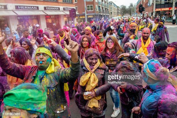 People cover each other with colored powder as they celebrate the Hindut religious festival of colors of Holi in The Hague on March 21 2019 For...