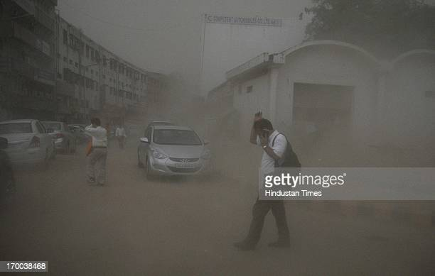 People cover their eyes during a dust storm at Connaught Place on June 6 2013 in New Delhi India Rain and strong winds lashed the capital Thursday...