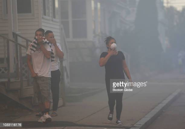 People cover their faces to protect themselves from heavy smoke from a fire on Bowdoin Street in Lawrence MA on Sep 13 2018 More than 60 fires and at...