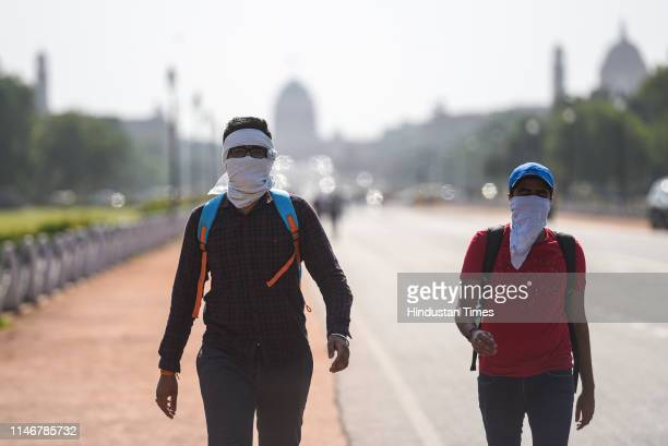 People cover their faces to protect themselves from the heat, at Rajpath, on May 28, 2019 in New Delhi, India. Delhi is reeling under hot and dry...
