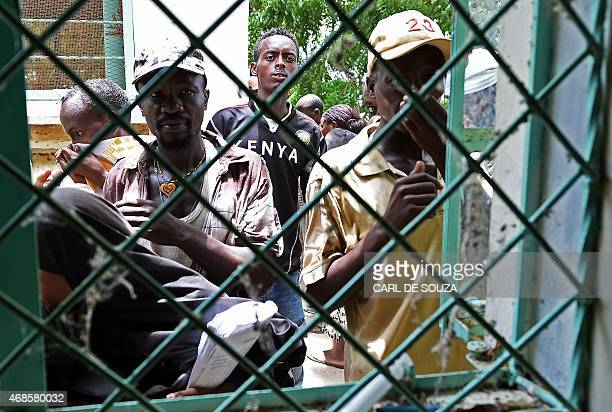 People cover their noses as they look through a metal window grate at the Garissa mortuary in the northeastern town of Garissa on April 4 to view the...