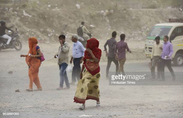People cover themselves during a suddem dust storm on May 2 2018 in Noida India A squall and dust storm followed by heavy rain lashed the national...