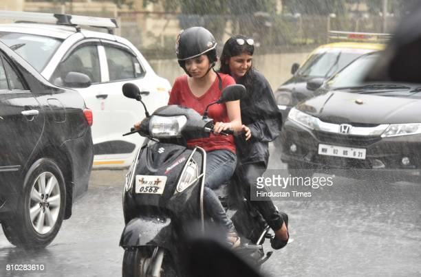 People cover themselves from rain at Peddar Road on July 6 2017 in Mumbai India