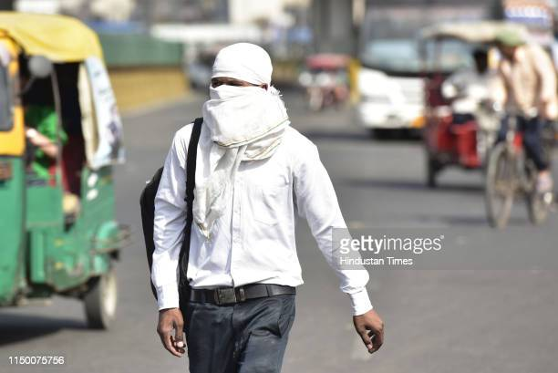 People cover themselves to beat the heat during a hot summer dayon June 14, 2019 in Noida, India. There was no let up in heatwave in Delhi NCR region...