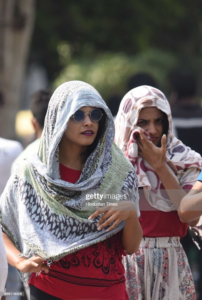 People cover to protect themselves during a hot sunny day as