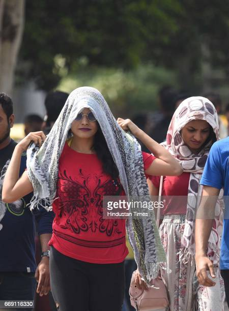 People cover to protect themselves during a hot sunny day as hot and dry weather prevails in many parts of the country at Red fort Old Delhi on April...