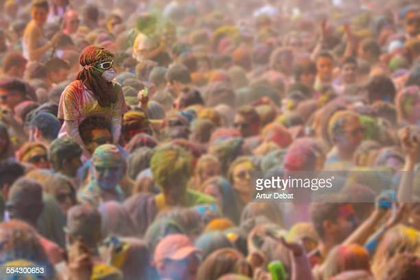 People covered with colorful powder in Holi party.